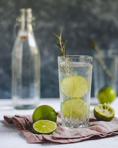 fruit sliced lemons beside drinking glass citrus fruit
