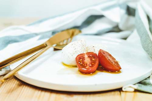plate sliced tomato and mozzarella cheese on white plate beside brass-colored knife and fork tomato