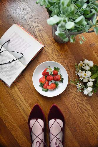 fruit strawberries on bowl beside book strawberry