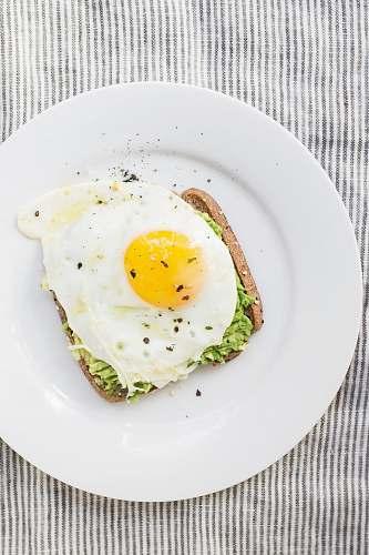 breakfast sunny side up egg, lettuce, bread on white ceramic plate healthy