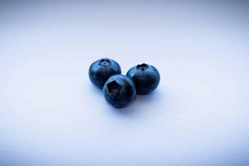 fruit three blackberries on white surface blueberry