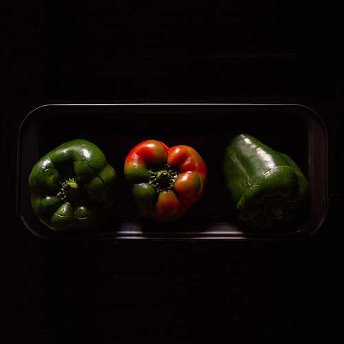 vegetable three orange and green bell peppers on black plate pepper