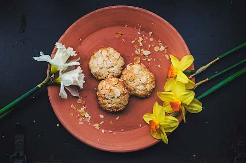 almond three round cookies on brown plate with petaled flowers flowers