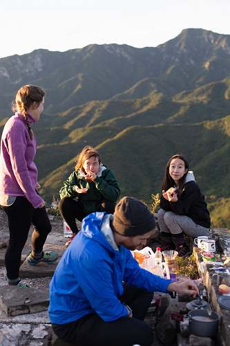 meal three woman and one man eating on top hill during daytime human