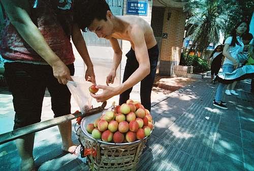 fruit topless man placing apples inside plastic bag apple