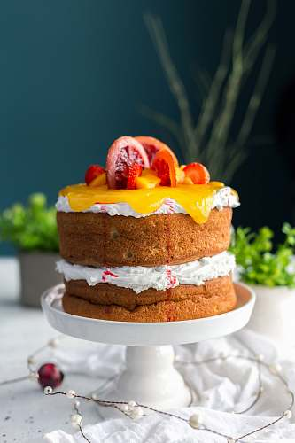 cake two-layered cake with citrus fruit and strawberry toppings dessert