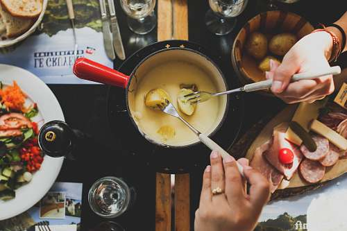fondue two person holding fork dipping food on sauce switzerland