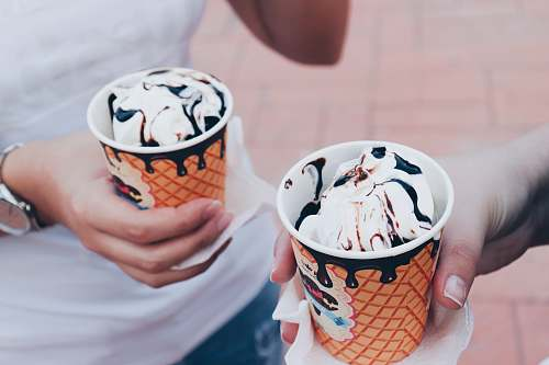 dessert two person holding white icings with disposable cap creme