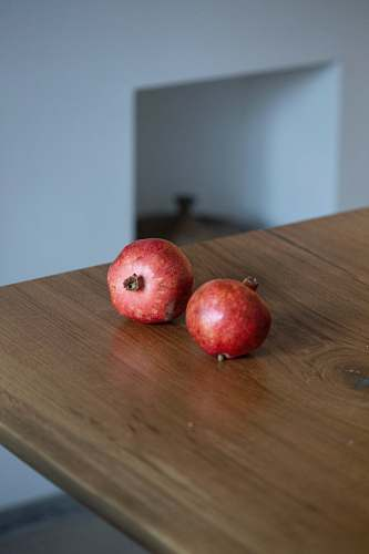 fruit two small round red fruits on brown wooden table apple