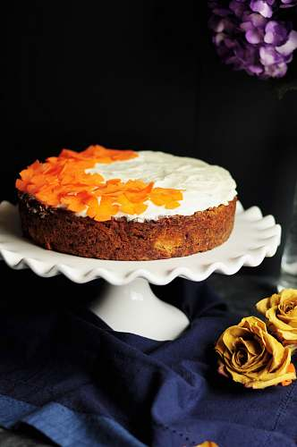 dessert white and orange icing-coated cake on scalloped edge white ceramic cake stand cake