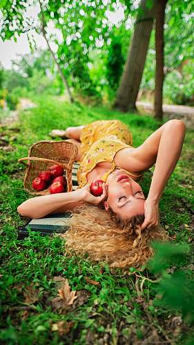 meal woman lying on green grass beside basket filled with red fruits vacation