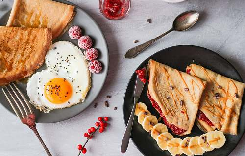 cutlery fried egg, bread and raspberry on plate spoon