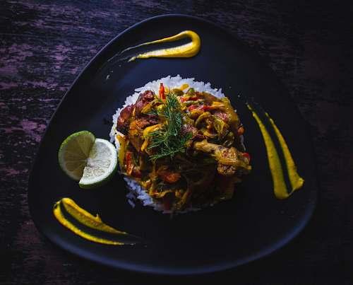 food cooked food served on black plate citrus fruit
