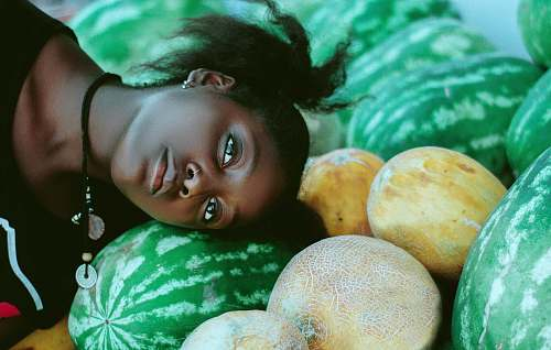 plant woman wearing black and white shirt leaning head on green watermelon fruits near cantaloupe melon