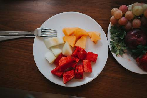 fork sliced watermelon and mango on plate with fork cutlery