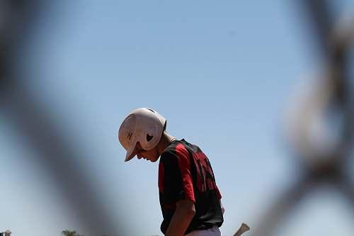 human baseball player looking down person