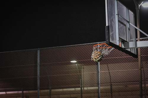 clothing basketball hoop near gray chain link fence during night sport