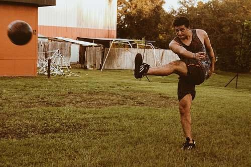 human man kicking brown soccer ball person