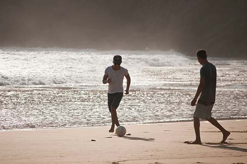 clothing men playing football in beach shorts