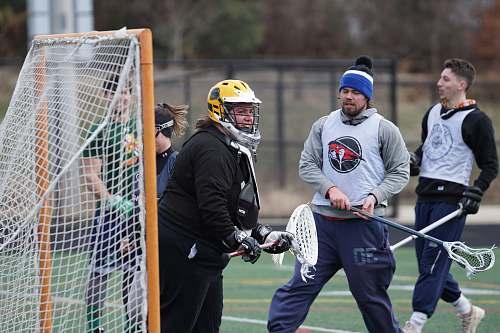 clothing people playing lacrosse during daytime helmet