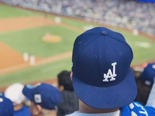 human selective focus photography of person wearing LA Dodgers cap looking at field person