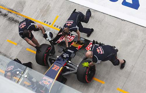 clothing three men at pit stop fixing formula one vehicle footwear