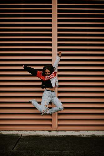 clothing woman jumping in front of brown wall people