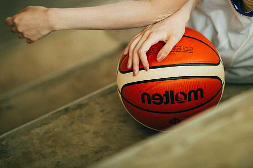 female person holding red and white Molten basketball ball woman