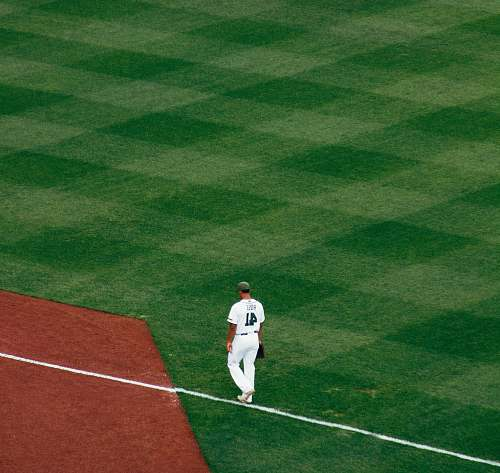 sport baseball player standing on field steps on white line at daytime sports