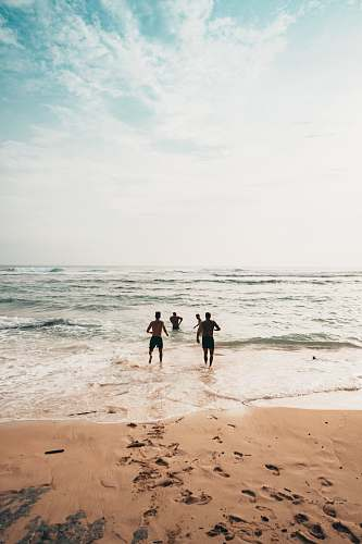 ocean men running toward beach coast