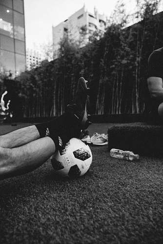 football gray scale photo of a person's feet on a football soccer