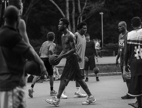 people grayscale photo of people playing basketball person