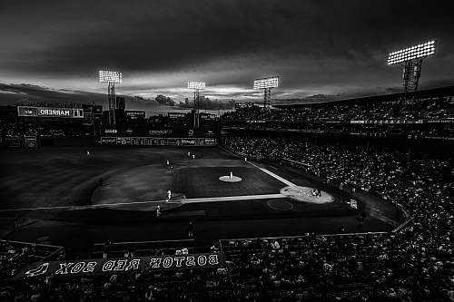 outdoors grayscale photography of baseball field with people on bleachers crowd