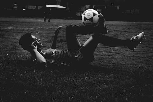 human man lying on field while playing soccer ball person