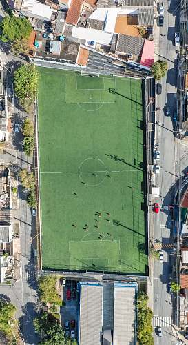 field aerial view of people playing football on court during daytime grey