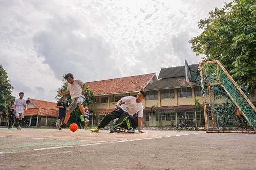 human men playing soccer during daytime person