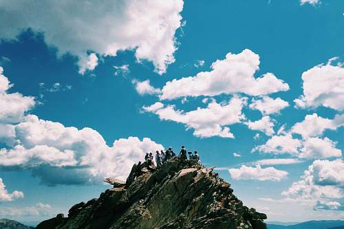 blue people on rock formation under white cloudy sky sky