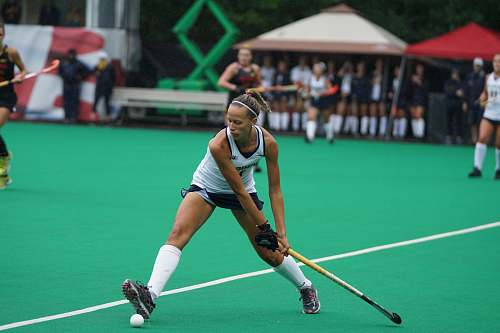 human woman holding hockey stick on field people