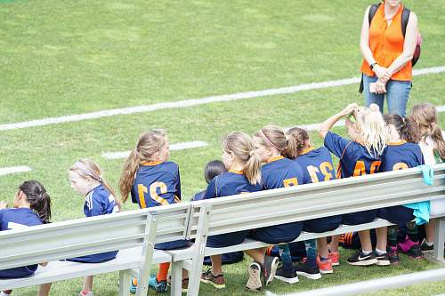 person all girl football team sitting on white bench beside green field people