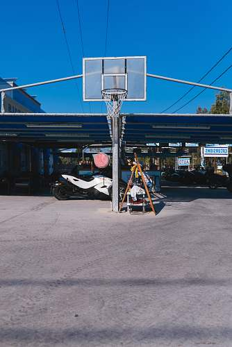 people basketball system in front of white sports bike parked under blue roofed space during daytime person