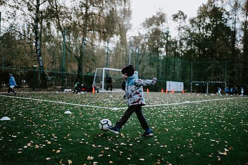 person boy playing soccer during daytime people
