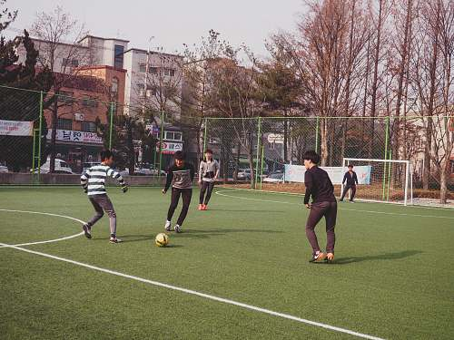 person boys playing soccer on field people
