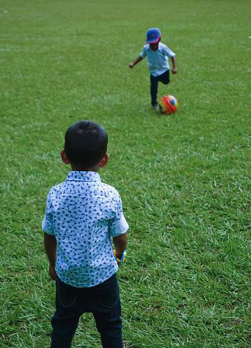 person child about to kick soccer ball and another boy standing people