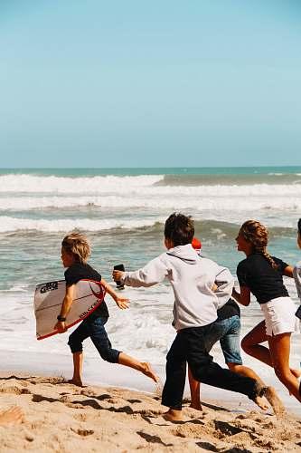 person children running on seashore across horizon nature