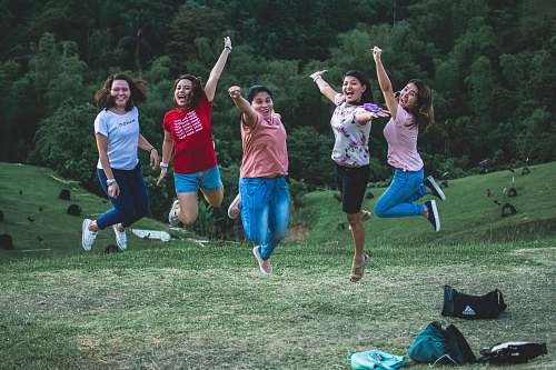 person five women jumping on green grass people