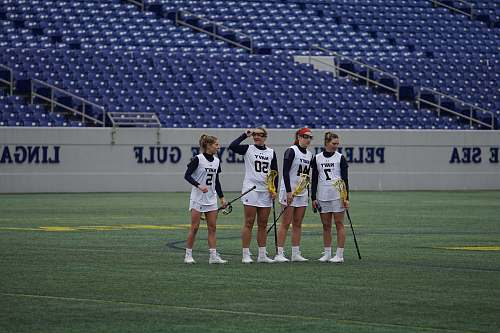 person four women holding lacrosse sticks on field during daytime field