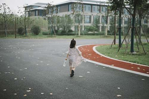 person girl holding clear plastic bottle walking on road people