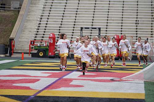 person girl's running on field holding lacrosse rackets people