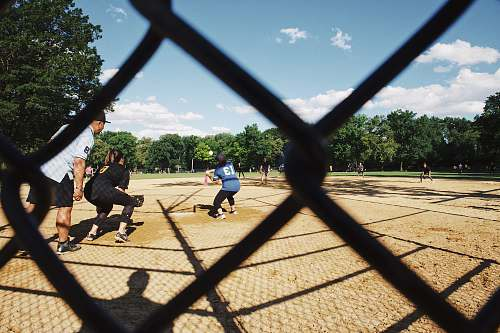 person gray cyclone fence across people playing baseball people