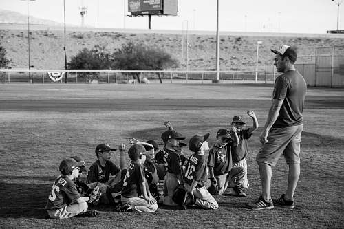person grayscale photo of boys football team in front of coach black-and-white